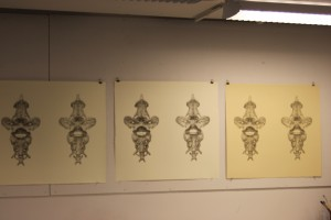 Various proofs of a print hanging in the Tamarind Institute. Different types of paper are also utilized here, and the artist and printer will choose the paper they think is best for the print.